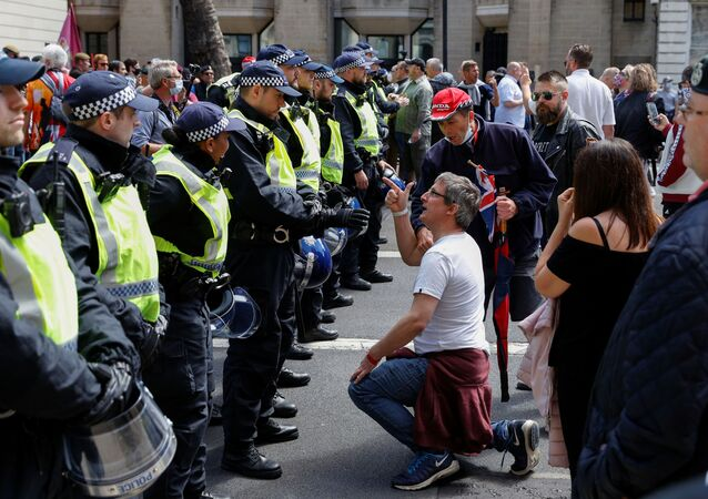 A demonstrator gestures as he kneels in front of the police officers during BLM protest in London