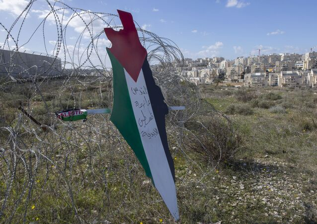 Placard with the colors of the Palestinian flags in front of Israeli barrier.