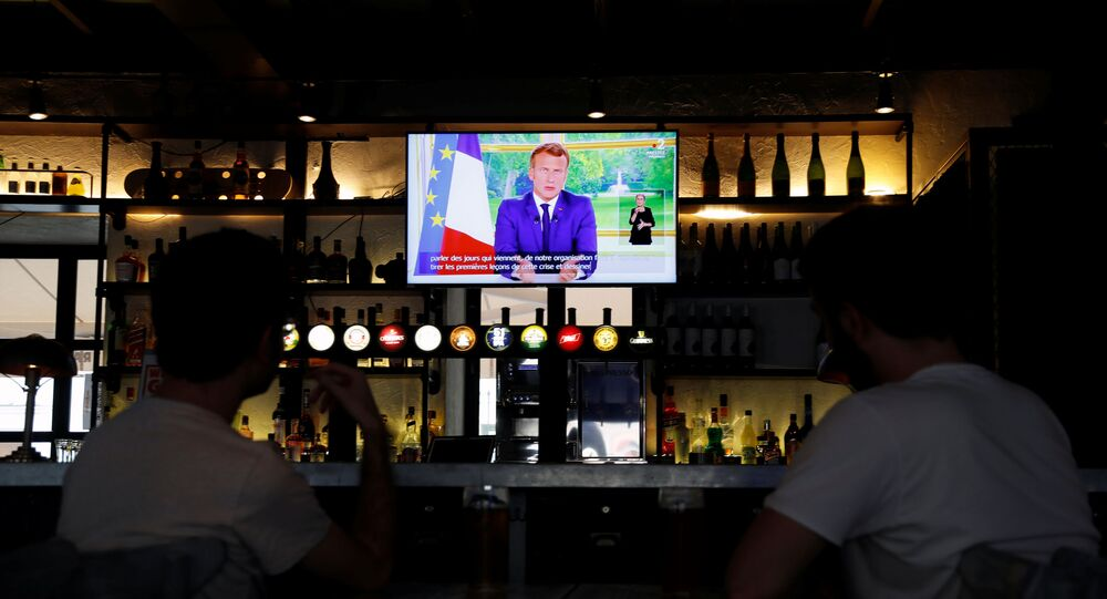 French President Emmanuel Macron is seen on a television screen in a pub while he addresses the nation