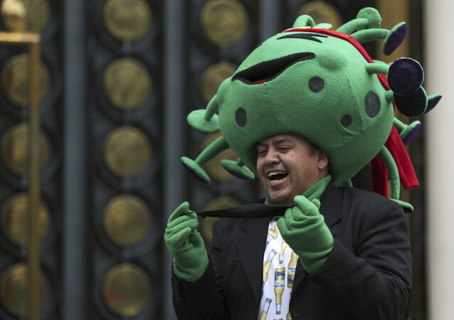 A street artist costumed as the new coronavirus laughs during a protest demanding the resumption of economic activities after not being able to earn a living since March because of the restrictions to curb the spread of COVID-19 in Mexico City, Thursday, June 11, 2020.