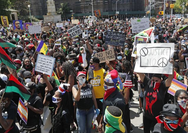 People gather to listen to speakers, rap artists and faith leaders during a Caribbean-led Black Lives Matter rally at Brooklyn's Grand Army Plaza, Sunday, June 14, 2020, in New York.