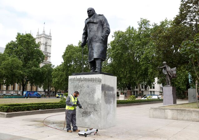 A council employee cleans graffiti from the statue of Winston Churchill at Parliament Square, in the aftermath of protests against the death of George Floyd who died in police custody in Minneapolis, London, Britain, June 8, 2020.
