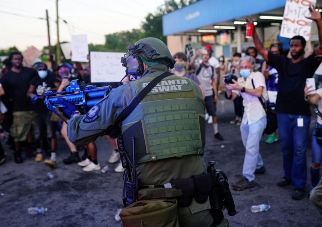 An Atlanta SWAT officer draws his weapon during a rally against racial inequality and the police shooting death of Rayshard Brooks, in Atlanta, Georgia, U.S. June 13, 2020.