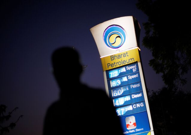 FILE PHOTO: A Bharat Petroleum oil pump station displays the price of unleaded petrol and Diesel fuel as a pedestrian walks past in New Delhi, India, 3 February 2016.