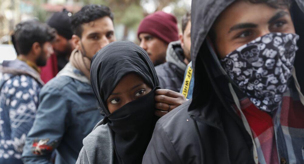 Migrants queue outside a supermarket to buy food near the Turkish-Greek border in Pazarkule, Edirne region, Turkey, Tuesday, 10 March 2020