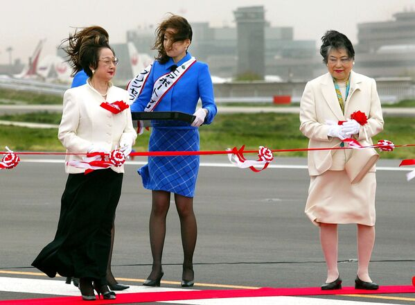 While in the strong wind, Japanese Land and Transport Minister Chikage Ohgi (L) and Chiba Governor Akiko Domoto (R) prepare to cut the ribbon for the opening ceremony of the second runway of the New Tokyo International Airport in Narita city, suburban Tokyo, 17 April 2002. The runway opened after years of delays, due to objections by landowners and farmers, to help the country cope with an expected influx of soccer fans and tourists ahead of the upcoming 2002 FIFA World Cup Korea/Japan - Sputnik International