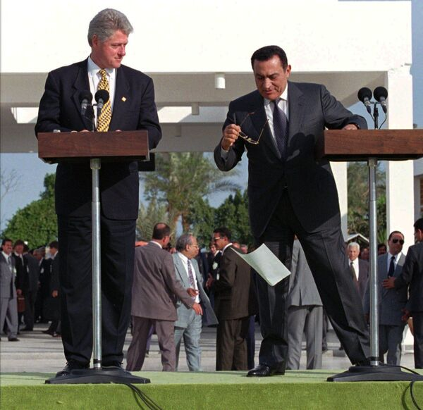 US President Bill Clinton looks on as his Egyptian counterpart Hosni Mubarak's papers are carried away by a gust of wind during the final address following their one-day Summit of Peacemakers in Sharm El Sheik, Wednesday March 13, 1996 - Sputnik International