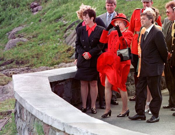 Queen Elizabeth II (C) looks out over the Atlantic Ocean as her dress blows in the wind as Canadian Heritage Minister Sheila Copps (L) and Newfoundland's Premier Brian Tobin watch at Signal Hill in St John's, Newfoundland, 25 June 1997 - Sputnik International