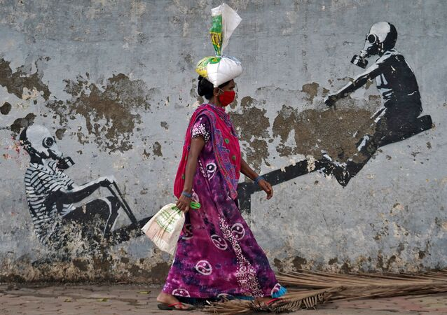 A woman wearing a protective face mask walks past a graffiti, after authorities eased lockdown restrictions that were imposed to slow the spread of the coronavirus disease (COVID-19), in Mumbai, India, June 12, 2020