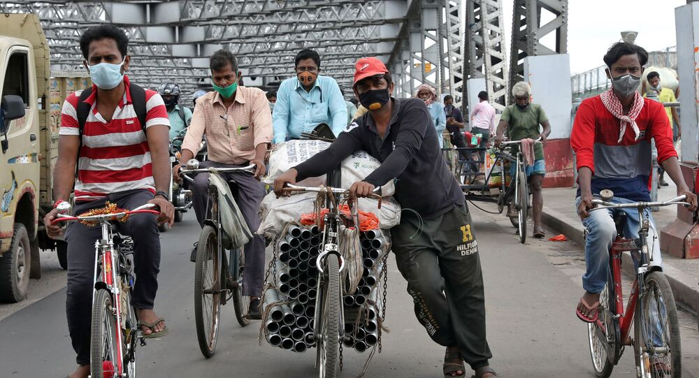 People wearing protective face masks ride their bicycles on Howrah bridge, after authorities eased lockdown restrictions that were imposed to slow the spread of the coronavirus disease (COVID-19), in Kolkata, India, June 12, 2020