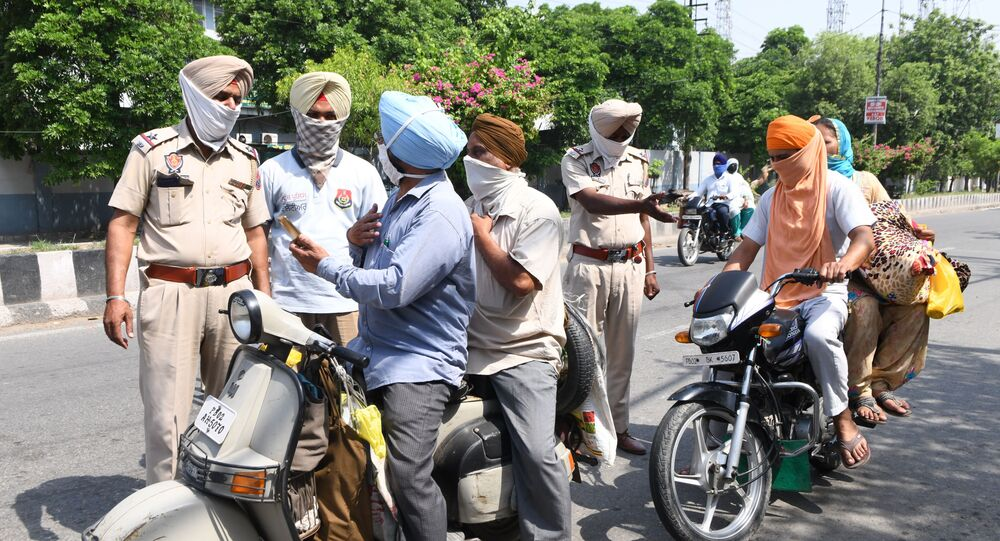 Police personnel check commuters after strict lockdown norms for weekends and public holidays were imposed as a preventive measure against the COVID-19 coronavirus, in Amritsar on June 14, 2020