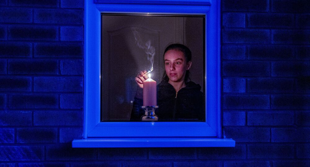 Woman lights a candle in the window of a home in Liverpool, England, after the Queen stressed the importance of maintaining the coronavirus lockdown during the Easter Bank Holiday weekend as she delivered what is believed to be her first Easter address, Saturday, April 11, 2020