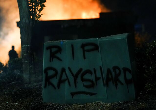 'RIP Rayshard' is seen written in spray paint as a Wendy's burns following a rally against racial inequality and the police shooting death of Rayshard Brooks, in Atlanta, Georgia, U.S. June 13, 2020