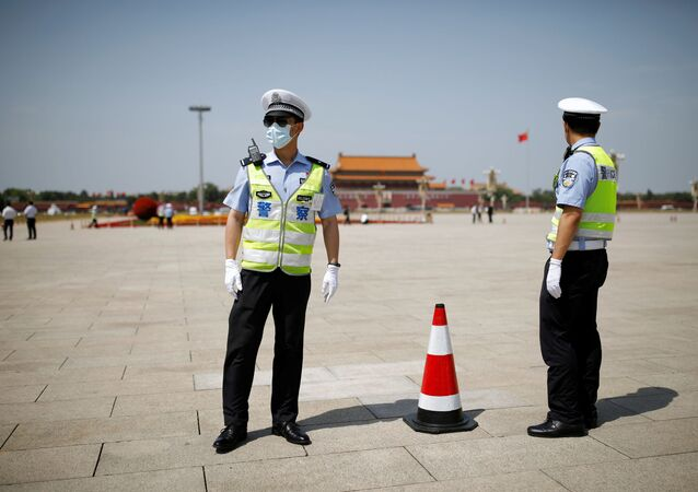 Police officers wearing face masks following the coronavirus disease (COVID-19) outbreak stand on Tiananmen Square before the closing session of the National People's Congress (NPC) in Beijing, China May 28, 2020.