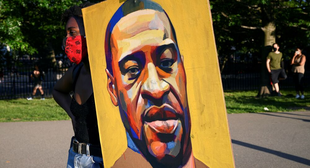 A demonstrator holds a painting depicting George Floyd as she protests against racial inequality in the aftermath of the death in Minneapolis police custody of George Floyd, in New York City, New York, U.S. June 9, 2020. Picture taken June 9, 2020.