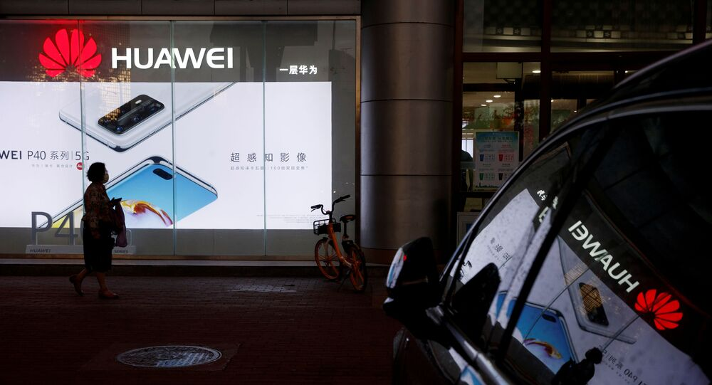 A woman walks past a Huawei store in Beijing, China May 28, 2020