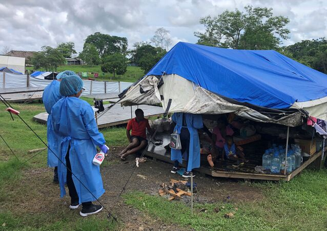 Medical staff talk to migrants at Lajas Blancas camp, where migrants from Africa, Cuba and Haiti are stranded due to the coronavirus disease (COVID-19) pandemic, during a visit by Panamanian authorities, in Darien Province, Panama June 5, 2020. Picture taken June 5, 2020.