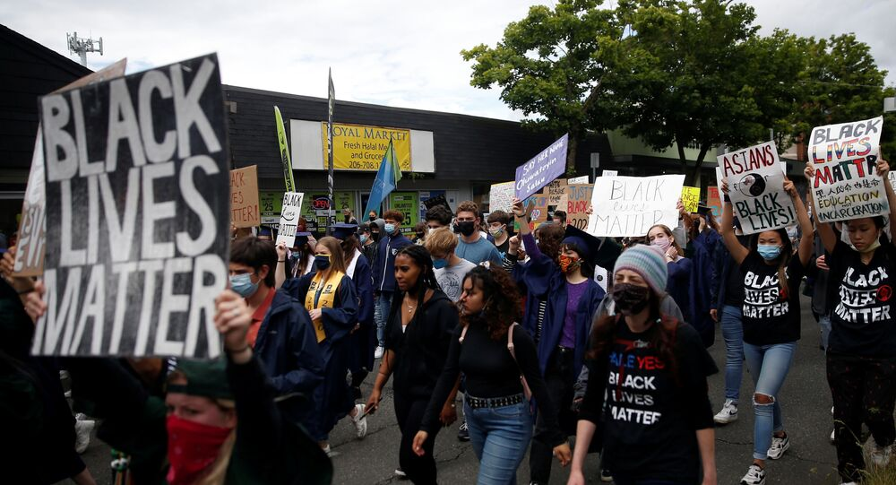 Demonstrators march up Lake City Way NE as Nathan Hale High School seniors join with others to protest against racial inequality in the aftermath of the death in Minneapolis police custody of George Floyd on their graduation day in Seattle, Washington, U.S. June 15, 2020