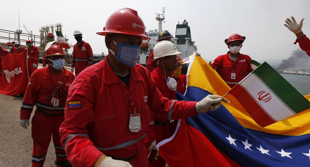 A Venezuelan oil worker holding a small Iranian flag attends a ceremony for the arrival of Iranian oil tanker Fortune at the El Palito refinery near Puerto Cabello, Venezuela, Monday, May 25, 2020