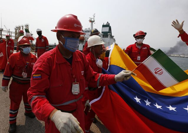 A Venezuelan oil worker holding a small Iranian flag attends a ceremony for the arrival of Iranian oil tanker Fortune at the El Palito refinery near Puerto Cabello, Venezuela, 25 May 2020