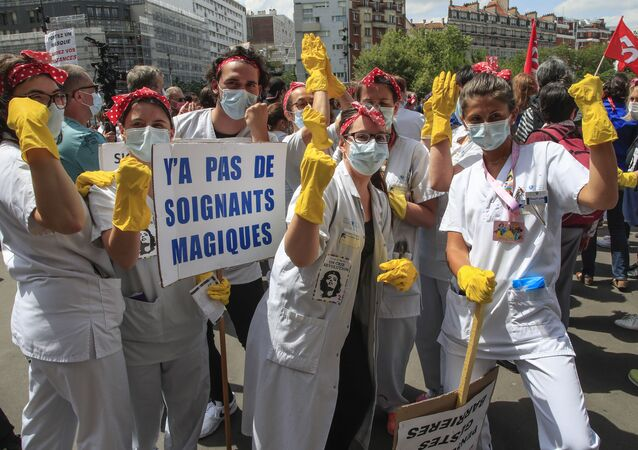 Medical personnel from the Robert Debre hospital wear masks to help curb the spread of the coronavirus holding a placard that reads, 'there are no magic medics' as they stage a protest in Paris, Thursday, June 11, 2020