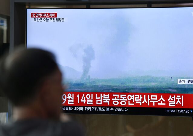 People watch a television news screen showing an explosion of an inter-Korean liaison office in North Korea's Kaesong Industrial Complex, at a railway station in Seoul on June 16, 2020