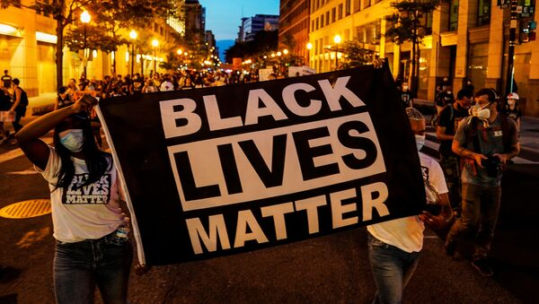 People hold up a Black Lives Matter banner as they march during a demonstration against racial inequality in the aftermath of the death in Minneapolis police custody of George Floyd, in Washington, U.S., June 14, 2020 - Sputnik International