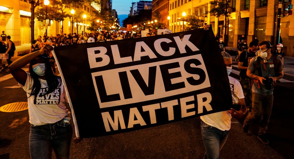 People hold up a Black Lives Matter banner as they march during a demonstration against racial inequality in the aftermath of the death in Minneapolis police custody of George Floyd, in Washington, U.S., June 14, 2020