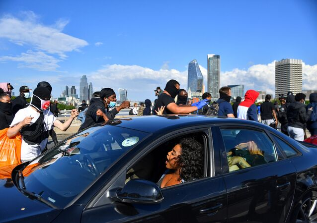 Protesters walk past a car on the Waterloo Bridge during a Black Lives Matter protest following the death of George Floyd in Minneapolis police custody, in London, Britain, June 13, 2020