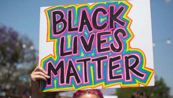 A participant holding a sign reading Black Lives Matter takes part in an All Black Lives Matter march, organized by Black LGBTQ+ leaders, in the aftermath of the death in Minneapolis police custody of George Floyd, in Hollywood, Los Angeles, California, U.S., June 14, 2020 - Sputnik International