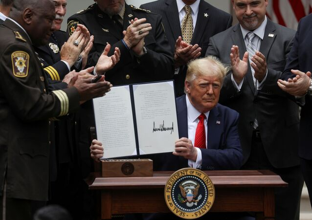 U.S. President Donald Trump displays an executive order on police reform during a signing ceremony in the Rose Garden at the White House in Washington, U.S., June 16, 2020.