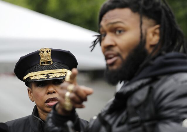 Seattle Police Chief Carmen Best, left, listens to activist Raz Simone as they talk near a plywood-covered and closed Seattle police precinct Tuesday, June 9, 2020, in Seattle, following protests over the death of George Floyd
