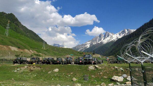 Indian army soldiers walk past their parked trucks at a makeshift transit camp before heading to Ladakh, near Baltal, southeast of Srinagar, June 16, 2020. - Sputnik International