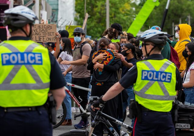 Two women hug in front of police as protesters march to highlight the deaths in the U.S. of Ahmaud Arbery, Breonna Taylor and George Floyd, and of Toronto's Regis Korchinski-Paquet, who died after falling from an apartment building while police officers were present, in Toronto, Ontario, Canada May 30, 2020.