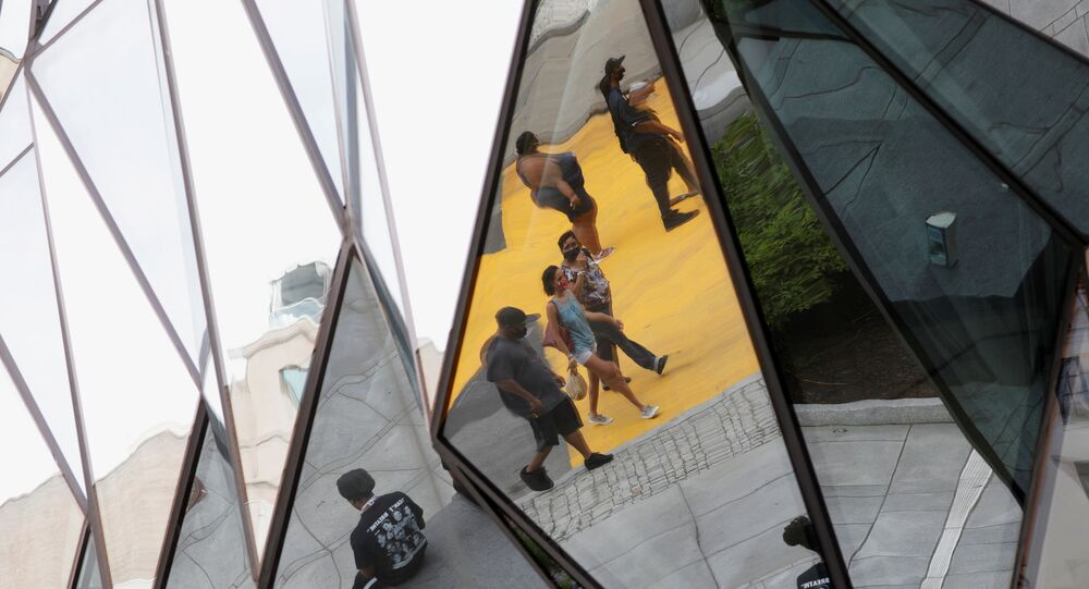 Pedestrians are seen reflected in a building mirror along Black Lives Matter Plaza near the White House in Washington, D.C. June 16, 2020.