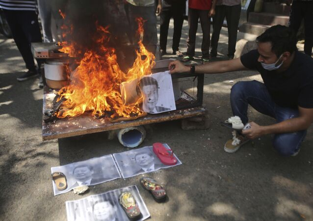 A man burns photographs of Chinese President Xi Jinping during a protest against the Chinese government in Jammu, India, Wednesday, June 17, 2020