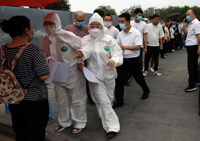 Medical workers in protective suits attend to people lining up outside a site for nucleic acid tests, following new cases of coronavirus disease (COVID-19) infections in Beijing, China June 17, 2020.  REUTERS/Tingshu Wang