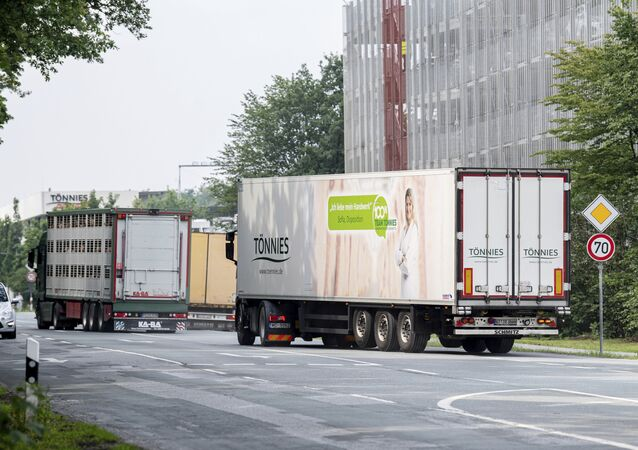 Trucks leave the Toennies meatpacking plant in Rheda-Wiedenbrueck, Germany, Wednesday, June 17, 2020. More than 400 new cases of COVID-19 have been recorded among workers at a large meatpacking plant in western Germany, authorities said Wednesday, in an outbreak that may have been linked to the easing of travel restrictions.( David Inderlied/dpa via AP)
