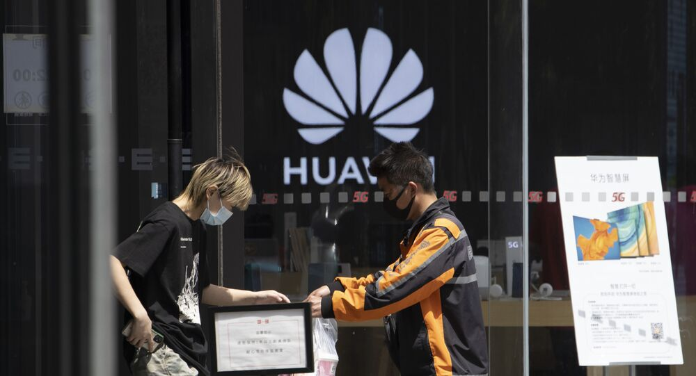 A delivery man hands over drinks near a Huawei retail store in Beijing on Monday, May 18, 2020