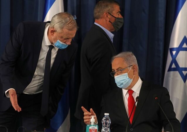 Israeli Prime Minister Benjamin Netanyahu speaks with Alternate Prime Minister and Defence Minister Benny Gantz, as they both wear a protective mask due to the ongoing coronavirus disease (COVID-19) pandemic, during the weekly cabinet meeting in Jerusalem June 7, 2020.