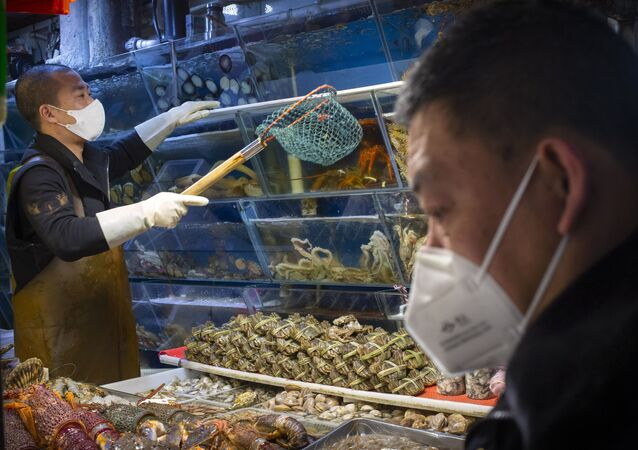 A customer wears a face mask as he shops for seafood at a market in Beijing, Saturday, March 14, 2020. The United States declared a state of emergency Friday as many European countries went on a war footing amid mounting deaths as the world mobilized to fight the widening coronavirus pandemic. For most people, the new coronavirus causes only mild or moderate symptoms, such as fever and cough. For some, especially older adults and people with existing health problems, it can cause more severe illness, including pneumonia.
