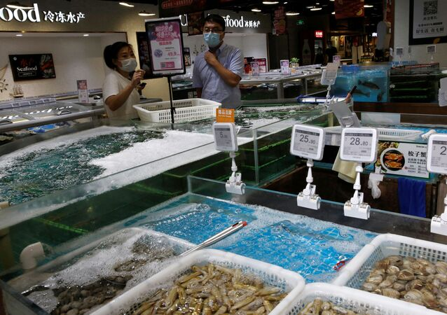 A staff member talks to a customer at a seafood section in JD.com's 7Fresh chain, following new cases of coronavirus disease (COVID-19) infections in Beijing, China June 17, 2020