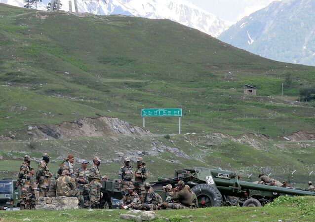 Indian army soldiers rest next to artillery guns at a makeshift transit camp before heading to Ladakh, near Baltal, southeast of Srinagar, June 16, 2020.