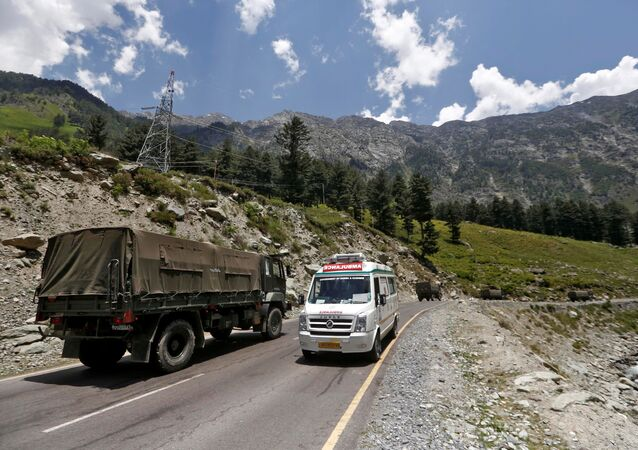 An ambulance moves past an Indian Army convoy along a highway leading to Ladakh, at Gagangeer in Kashmir's Ganderbal district June 18, 2020.