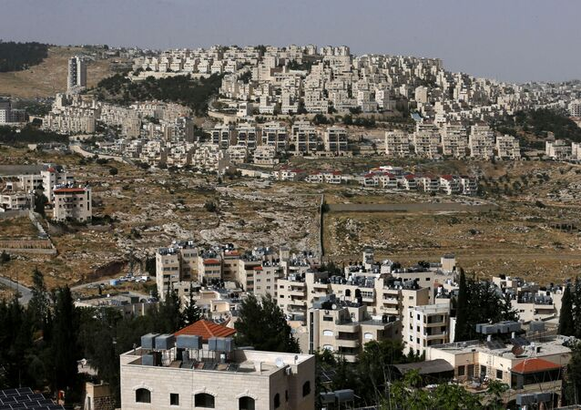 A view shows the Israeli settlement of Har Homa in the background as Palestinian houses are seen in the foreground, in the Israeli-occupied West Bank, May 19, 2020. Picture taken May 19, 2020.