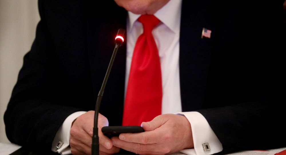 U.S. President Donald Trump is seen tapping the screen on a mobile phone during a roundtable discussion on the reopening of small businesses in the State Dining Room at the White House in Washington, U.S., June 18, 2020