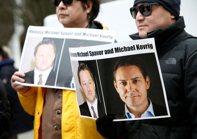 People hold signs calling for China to release Canadian detainees Michael Spavor and Michael Kovrig during an extradition hearing for Huawei Technologies Chief Financial Officer Meng Wanzhou at the B.C. Supreme Court in Vancouver, British Columbia, Canada