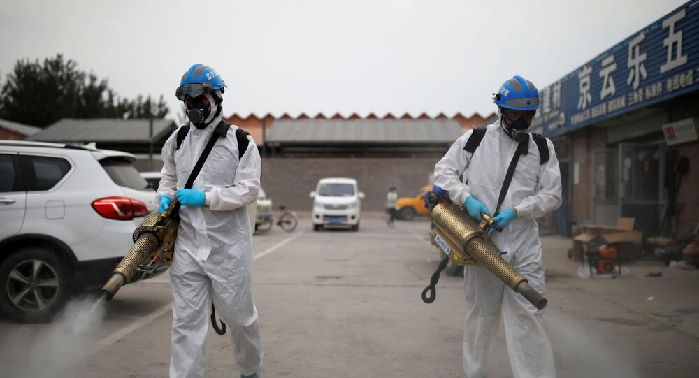 Volunteers from the Blue Sky Rescue team, in protective suits, disinfect the Nangong comprehensive market following a new outbreak of the coronavirus disease (COVID-19) in Beijing, China, June 18, 2020. Picture taken June 18, 2020. REUTERS/Carlos Garica Rawlins