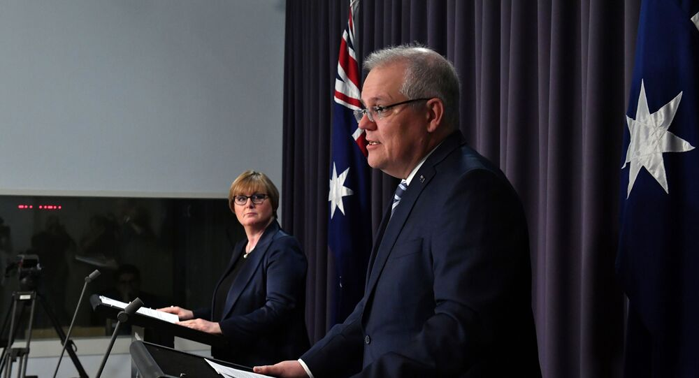 Prime Minister Scott Morrison speaks as Minister for Defence Linda Reynolds looks on during a press conference, revealing a state-based cyber attack targeting Australian government and business, at Parliament House in Canberra, Australia, 19 June 2020.