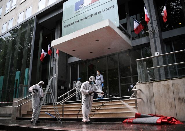 Employers clean the entrance of the  French Health Ministry soiled by red paint after French activists of Attac stage a protest in support of medical workers outside the Ministry in Paris on June 20, 2020.